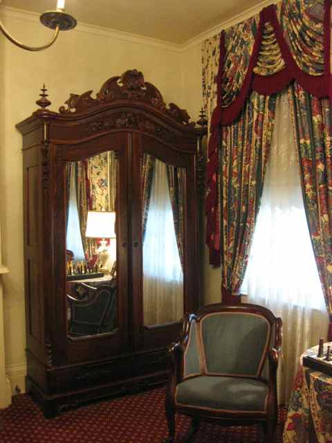 a beautiful mirrored armoire and some more fringed drapery